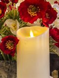 White candle with red and white flowers Royalty Free Stock Images