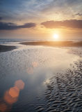 Beautiful vibrant Summer sunset over golden beach landscape with Royalty Free Stock Images