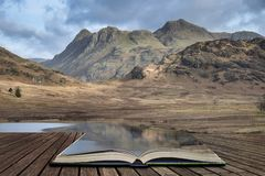 Beautiful vibrant sunrise landscape image of Blea Tarn in UK Lake District  coming out of pages in story book. Stunning sunrise landscape image of Blea Tarn in stock illustration