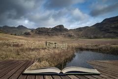 Beautiful vibrant sunrise landscape image of Blea Tarn in UK Lake District  coming out of pages in story book. Stunning sunrise landscape image of Blea Tarn in royalty free illustration
