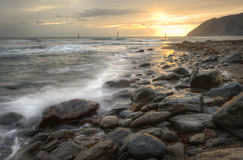 Beautiful vibrant sunrise over ocean with rocks. Lovely image of sunrise over incoming tide with rocky foreground and cliffs in background Royalty Free Stock Photos
