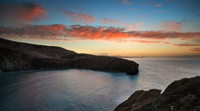 Beautiful vibrant sunrise over rocky coastline. Stunning vibrant sunrise over rocky coastline Stock Photos