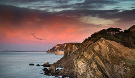 Beautiful vibrant sunrise over rocky coastline. Stunning vibrant sunrise over rocky coastline Stock Image