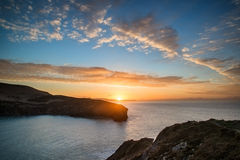 Beautiful vibrant sunrise over rocky coastline Stock Image
