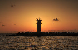 Beautiful Vibrant Sunrise Sky Over Calm Sea Water And Lighthouse. With Breakwater Royalty Free Stock Photos