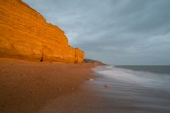 Beautiful vibrant sunset landscape image of Burton Bradstock gol. Beautiful sunset landscape image of Burton Bradstock golden cliffs in Dorest England Stock Image