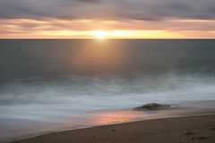 Beautiful vibrant sunset landscape image of Burton Bradstock gol. Beautiful sunset landscape image of Burton Bradstock golden cliffs in Dorest England Stock Images