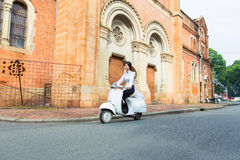 Beautiful Vietnamese girl in long dress (Ao dai) with conincal hat is driving on old white motorbike Royalty Free Stock Photo