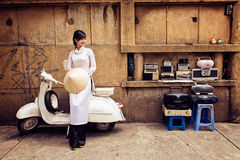 Beautiful Vietnamese girl in long dress (Ao dai) with conincal hat is sitting on old white motorbike Stock Photo