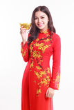Beautiful Vietnamese woman with red ao dai holding lucky new year ornament - stack of gold Stock Photo