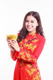 Beautiful Vietnamese woman with red ao dai holding lucky new year ornament - stack of gold Stock Photos
