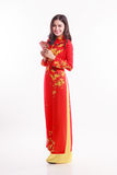 Beautiful Vietnamese woman with red ao dai holding red packet. Li xi on white background Stock Photos