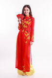 Beautiful Vietnamese woman with red ao dai holding red packet. Li xi on white background Royalty Free Stock Image
