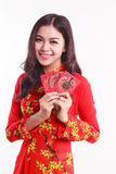 Beautiful Vietnamese woman with red ao dai holding red packet. Li xi on white background Royalty Free Stock Photo