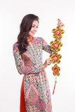 Beautiful Vietnamese woman wearing impression ao dai holding lucky decorate object Royalty Free Stock Image