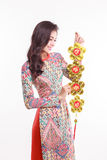 Beautiful Vietnamese woman wearing impression ao dai holding lucky decorate object Royalty Free Stock Images