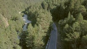 Beautiful view from above car moving along road among green forest to mountains. Car driving at highway on mountain background aerial view stock video footage