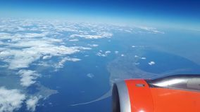 Beautiful view from the airplane window to the blue sky and white clouds, white clouds float above the ground.  stock footage