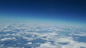 Beautiful view from the airplane window to the blue sky and white clouds, white clouds float above the ground.  stock video