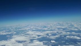 Beautiful view from the airplane window to the blue sky and white clouds, white clouds float above the ground.  stock video footage