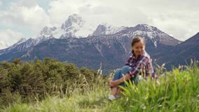 Beautiful view of Alps mountains and blurred image of tourist woman sitting on a green meadow. Travel in Alps mountains. 4k stock footage