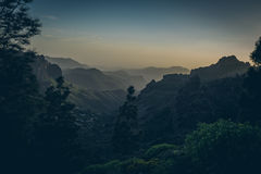Beautiful view of amazing tropical scenery with mountain valleys above wide open sea in golden evening light at sunset Stock Photo