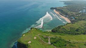 Beautiful view in Bali with golf field and turquoise ocean with waves, aerial. Beautiful view in Bali with golf field and turquoise ocean with waves stock footage
