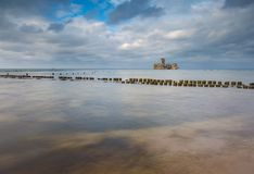 Beautiful view on Baltic sandy coast with old military buildings from world war II and wooden breakwaters. Royalty Free Stock Photos