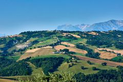 A beautiful view with blue skies over the hills of Le Marche in Italy with Monti Sibilini in the background. A beautiful view with blue skies over the hills of royalty free stock images