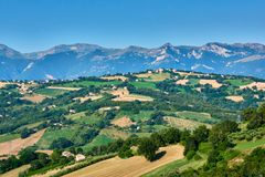 A beautiful view with blue skies over the hills of Le Marche in Italy with Monti Sibilini in the background. A beautiful view with blue skies over the hills of stock photos