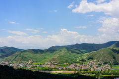 A beautiful view of the blue sky, white clouds, green hills, villages, winding roads Royalty Free Stock Image