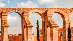 Beautiful view of brick and stone arches in an orange color of an old bullring. Wonderful sunny day with a blue sky with white clouds in Zacatecas Mexico stock photo