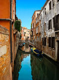 Beautiful view of the bridge over venetian сanal. Beautiful view of the bridge over narrow venetian сanal with boats and colorful facades of old medieval royalty free stock photo