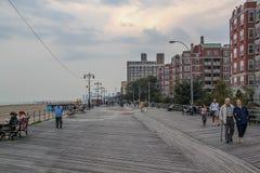 Beautiful view of Brighton Beach coast. People walking on sidewalk along high buildings.  USA. New York. royalty free stock images