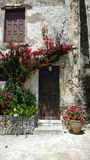 Beautiful view of the building with entrance door and blooming flowers around her. Stock Image