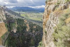 Beautiful view of a canyon, Tajo de Ronda with a valley in the background with cultivated areas. Seen from the city of Ronda on a wonderful and sunny day in the stock images