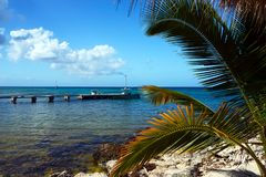 Beautiful view of the Caribbean Sea, the blue sea, a broken bridge and a boat from a sandy beach with blue chairs on the island of stock photo