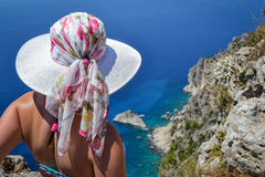 Girl looking over the sea from cliff. Beautiful view from the cliffs of Corfu Stock Photo