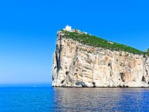 A beautiful view of the cliffs with the lighthouse Capo Caccia. Sardinia, Italy royalty free stock image