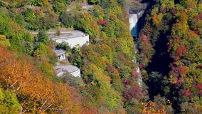 Beautiful view of colorful autumn foliage on the mountain with the high waterfall and cars running on the curved road