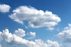 White clouds on a blue sky. A beautiful view of cottony white clouds on a blue sky royalty free stock photography