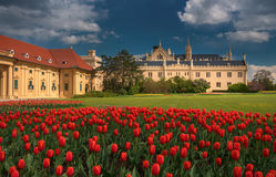 Beautiful view of the Czech castle Lednice, with a cloudy thunderous sky and a lot of red tulips. Stock Photo