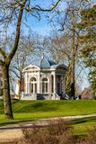 Beautiful view of a dirt road, green grass, trees and over the hill the Tea dome or Gloriette in Proosdij Park stock photography