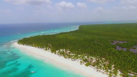 A beautiful view from the drone on a green island with white sand beaches and crystal clear ocean water. In slow-motion stock video