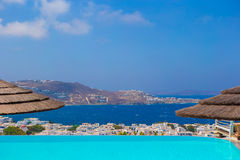Beautiful view from the edge of infinity pool to the sea and the mountains in the greek town of Mykonos Royalty Free Stock Photos