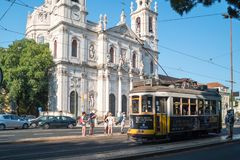 Beautiful view of Estrela Basilica facade and historic yellow tram 28 at tram stop. Lisbon, Portugal royalty free stock photography
