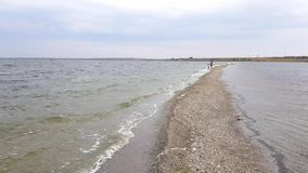 Beautiful view of family walking along spit. Mom and little daughter walk on the spit in early autumn stock video