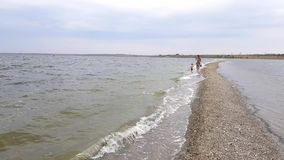 Beautiful view of family walking along spit. Mom and little daughter walk on the spit in early autumn stock footage