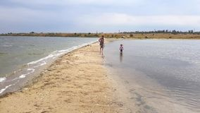 Beautiful view of family walking along spit. Mom and little daughter walk on the spit in early autumn stock video footage
