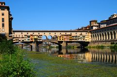 A Beautiful view of the famous Old Bridge Ponte Vecchio and Uffizi Gallery with blue sky in Florence as seen from Arno Royalty Free Stock Images